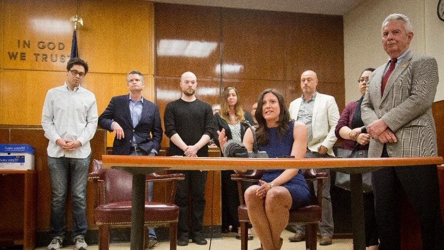 Surrounded by fellow jurors, Jennifer O'Connor, seated, speaks during a press conference after a judge declared a mistrial for Pedro Hernandez at Manhattan Supreme Court, Friday, May 8, 2015, in New York.   A jury was hung after 18 days of deliberating the case against Hernandez, charged with murder in the 1979 disappearance of 6-year-old Etan Patz.   (AP Photo/Bebeto Matthews)