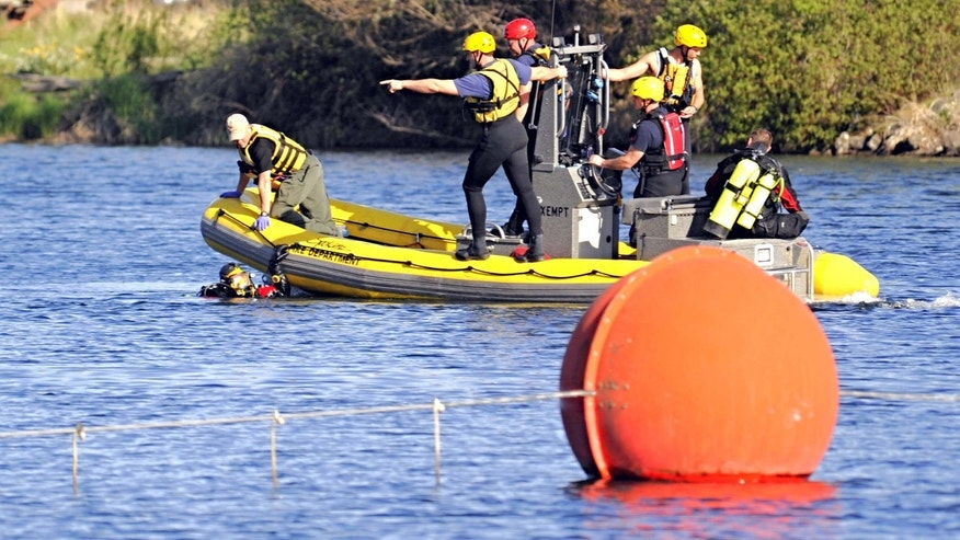 May 7, 2015: Rescue personnel, with divers in the water, search the area of a small plane crash in the Spokane River.