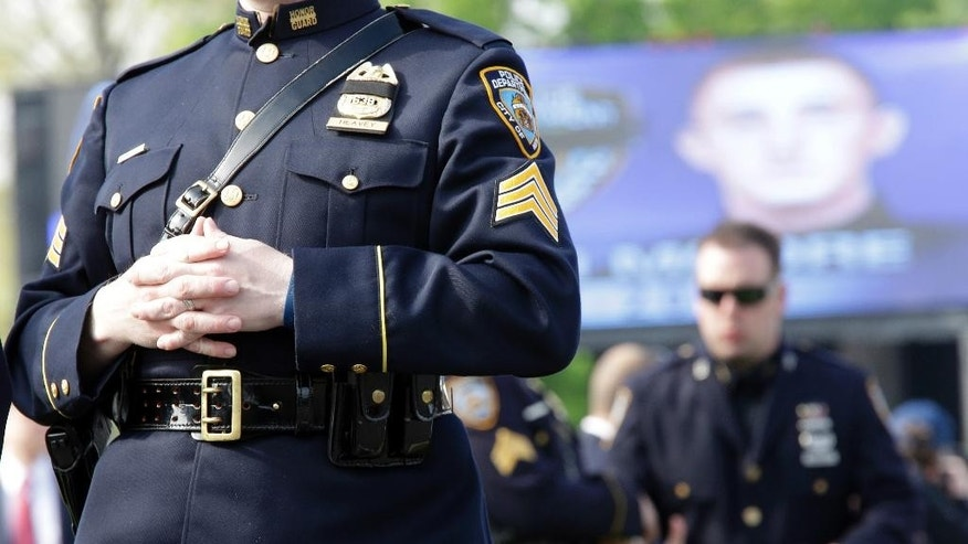 A member of the police honor guard has his badge covered in mourning as he arrives for the funeral mass for New York City police officer  Brian Moore, Friday, May 8, 2015, at the St. James Roman Catholic church in Seaford, N.Y.  As many as 30,000 police officers from across the United States are expected to pay their respects at the Long Island funeral for the young  police officer slain on patrol. (AP Photo/Mary Altaffer)