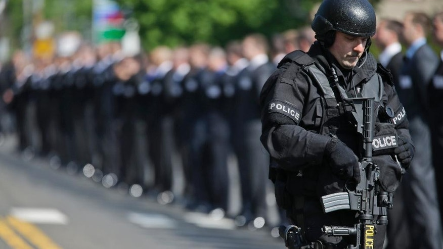 A heavily armed police officer stands guard near the funeral Mass for New York Police Department Officer Brian Moore,  Friday, May 8, 2015, at the St. James Roman Catholic Church in Seaford, N.Y. The 25-year-old died Monday, two days after he was shot in Queens, while on patrol. (AP Photo/Mary Altaffer)