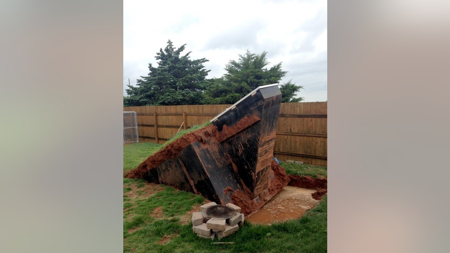 This photo by KOCO shows a storm shelter that came out of the ground after four inches of rain fell Tuesday night, May 5, 2015 through Wednesday morning in Noble, Okla. a surrounding community of Norman. The owner had to find alternative cover during Wednesday evenings' storms said KOCO reporter Morgan Chesky. Spring storms spawned more than a dozen suspected tornadoes in the southern Plains, destroying dozens of homes, causing flooding and forcing the evacuation of Oklahoma City's main airport. At least 12 people were injured but there were no reports of deaths. (Morgan Chesky/KOCO via AP)