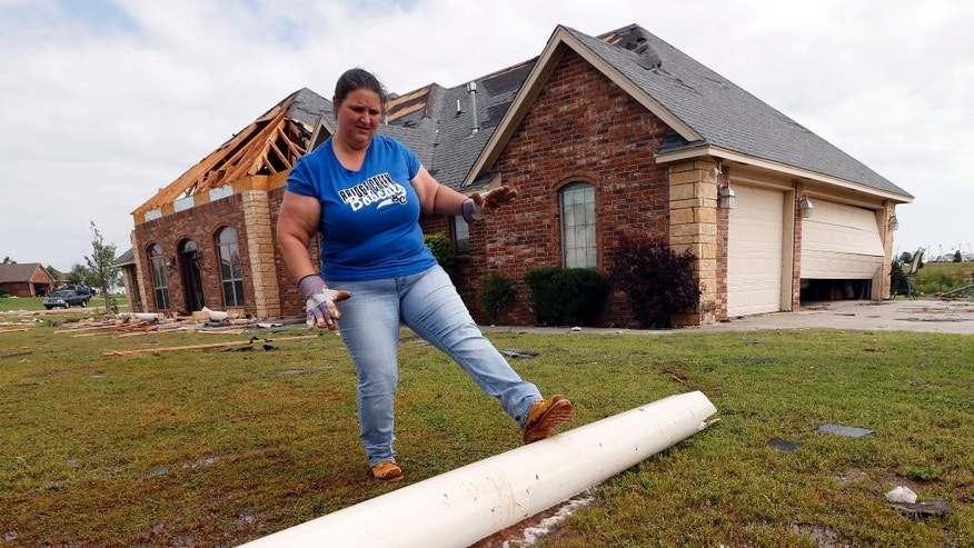 Fantasy Gentner lends a hand removing debris from a friend's home on Thursday, May 7, 2015 in Bridge Creek, Okla.  The pipe was once the center support for a brick column. Communities in several southern Plains states set to work cleaning up Thursday after a night of storms that spawned dozens of tornadoes, assessing the damage under sunny skies but with the threat of even worse weather on the horizon. (Steve Sisney/The Oklahoman via AP)