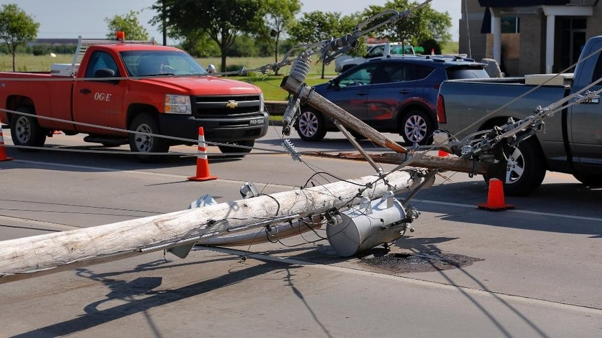 Cars drive past a downed power pole in Norman, Okla., Thursday, May 7, 2015. Communities in several southern Plains states set to work cleaning up Thursday after a night of storms that spawned dozens of tornadoes, assessing the damage under sunny skies but with the threat of even worse weather on the horizon. (Chris Landsberger/The Oklahoman via AP)
