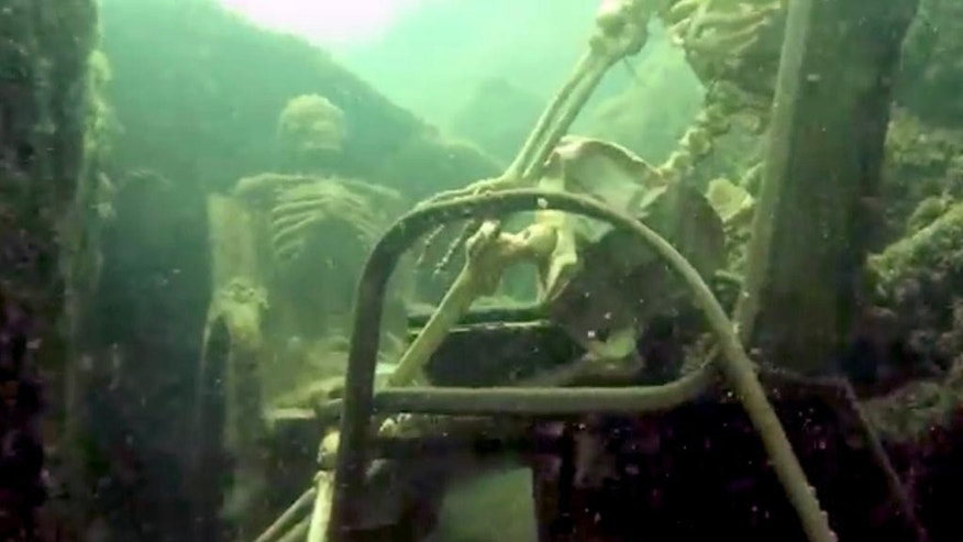 In this frame from video provided by the La Paz Sheriffs' Office, fake skeletons are strategically placed to appear as if they were sitting together with their lawn chairs bound to large rocks in the Colorado River near the Arizona and California border.  A Phoenix couple has claimed responsibility for the two fake skeletons.  The husband and wife approached the La Paz County Sheriff's Office earlier this week and brought a photo as proof they were behind the prank in Parker, Ariz. Lt. Curt Bagby says there are no plans to press charges and considers the incident harmless. (AP Photo/La Paz Sheriff's Office)
