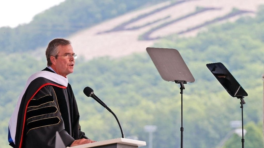 Former Florida Gov. Jeb Bush, at podium, delivers the commencement address at Liberty University in Williams Stadium at the school in Lynchburg, Va., Saturday, May 9, 2015.   (AP Photo/Steve Helber)