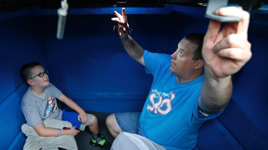 David Wheeler demonstrates his flashlight attached to the ceiling of his storm shelter, in Oklahoma City, Friday, May 8, 2015. At left is his son, Gabriel, age 10. Wheeler has the shelter stocked with blankets and flashlights. (AP Photo/Sue Ogrocki)