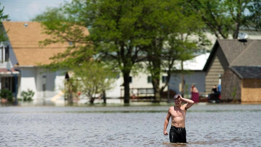 Brandon Houts walks from his house through floodwater to get supplies from a friend Thursday, May 7, 2015, in De Witt, Neb. Communities in several southern Plains states set to work cleaning up Thursday after a night of storms that spawned tornadoes, assessing the damage under sunny skies but with the threat of even worse weather on the horizon. (Matt Ryerson/The Journal-Star via AP)