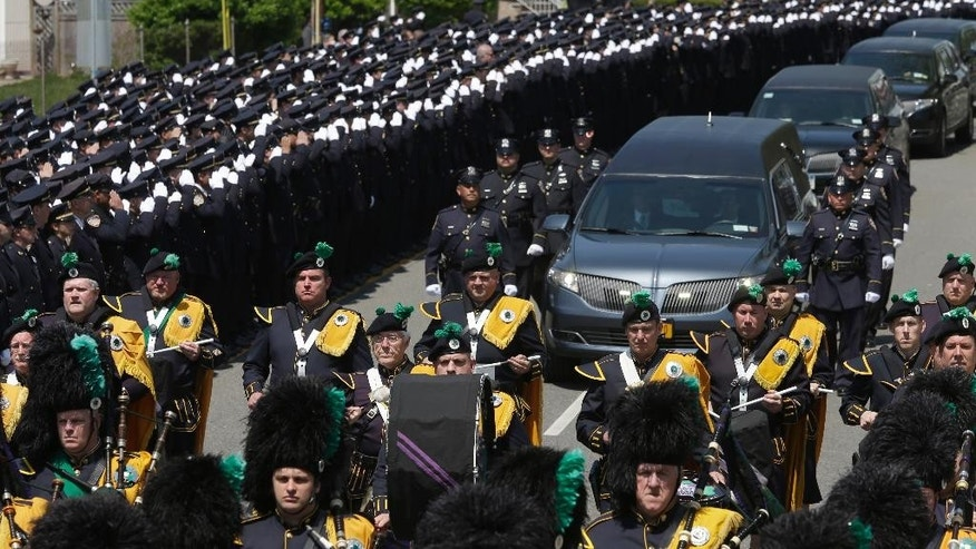 Police officers salute as the procession for police officer Brian Moore passes after his funeral mass,  Friday, May 8, 2015, at the St. James Roman Catholic church in Seaford, N.Y. The 25-year-old died Monday, two days after he was shot in Queens.  (AP Photo/Mary Altaffer)
