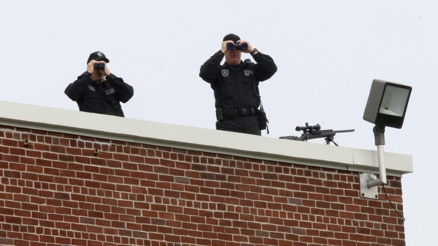 Police snipers survey the area from the roof of an elementary school before the funeral Mass of New York Police Department Officer Brian Moore, Friday, May 8, 2015, at the St. James Roman Catholic Church in Seaford, N.Y. As many as 30,000 police officers from across the United States were expected to pay their respects at the Long Island funeral for Moore, who was slain while on patrol. (AP Photo/Mary Altaffer)