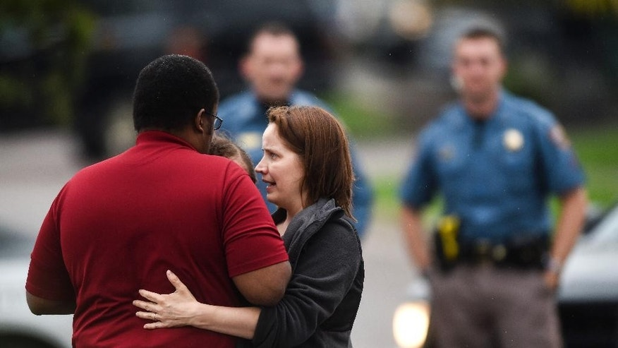 A woman hugs her husband, Glenn Thomas, a Colorado Springs police officer, after he emerged safe from inside Hobby Lobby off 8th Street where there was a shooting Friday, May 8, 2015. Thomas, who was off duty, was inside the store at the time of the shooting. (Michael Ciaglo/The Gazette via AP)