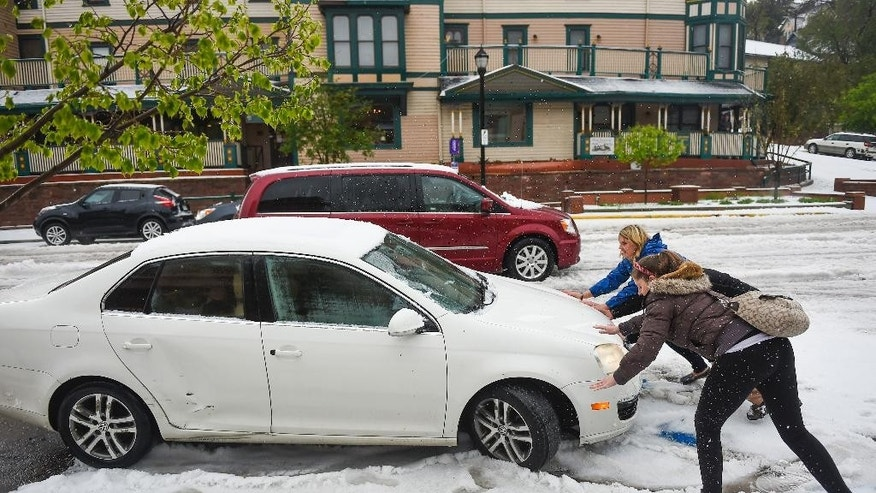 Passersby help push a car out of a gutter after about two inches of hail fell on Manitou Springs, Colo. Saturday, May 9, 2015. (Michael Ciaglo/The Gazette via AP)