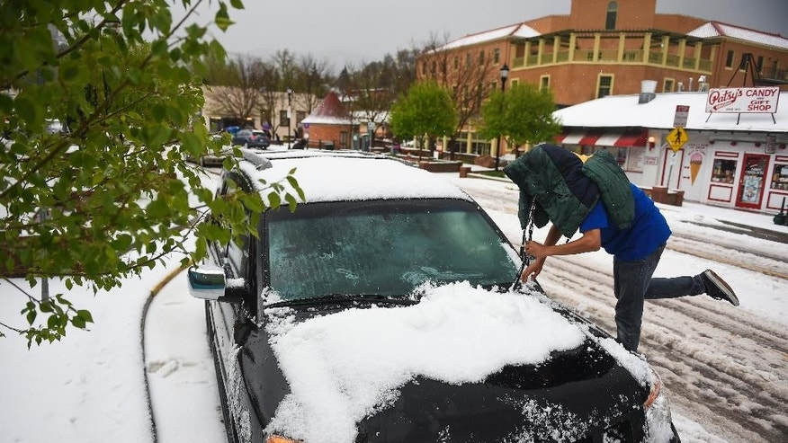 Wesley Ford stands on a tire as he clears about two inches of hail off a car after a large storm passed over Manitou Springs, Colo. on Saturday, May 9, 2015. (Michael Ciaglo/The Gazette via AP)
