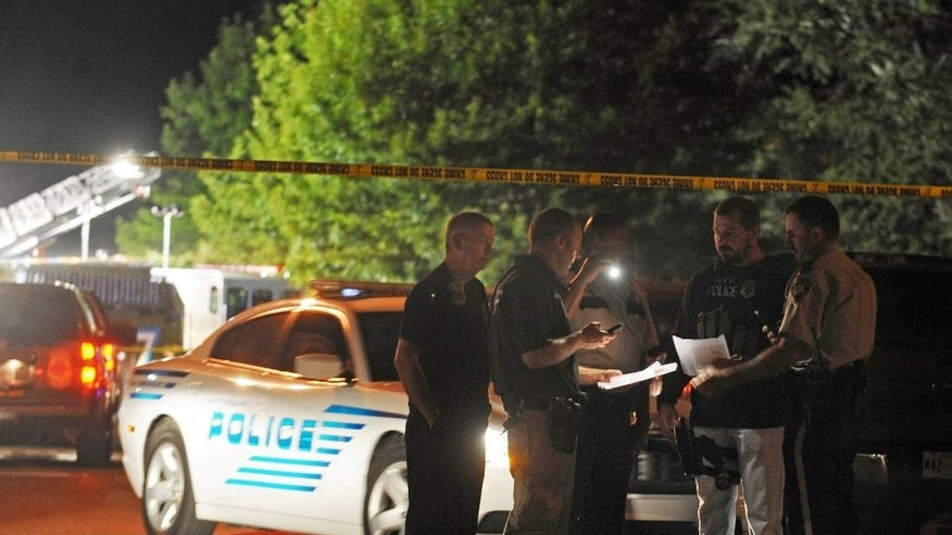 Hattiesburg lawmen study information on suspects wanted for the fatal shooting of two Hattiesburg, Miss., police officers, Saturday night, May 9, 2015. Authorities are conducting a manhunt for the suspects. (Ryan Moore/WDAM-TV via AP) NO SALES