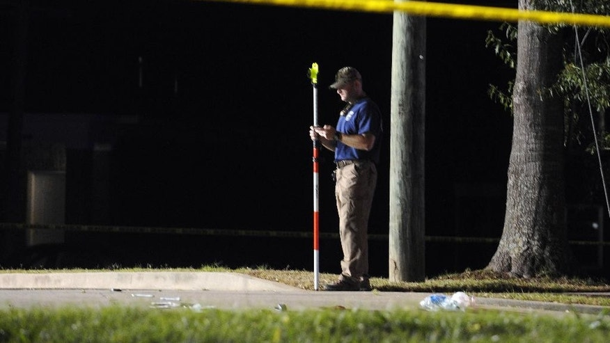 A Hattiesburg, Miss., lawman investigates the scene where two Hattiesburg police officers were shot to death, Saturday night, May 9, 2015. Authorities are conducting a manhunt for the suspects. (Ryan Moore/WDAM-TV via AP) NO SALES