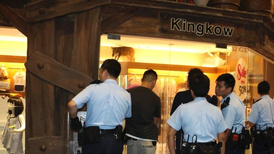 In this Sunday, May 10, 2015 photo, police officers watch a wild boar, top, at a children's clothing store at a mall in Hong Kong. The Hong Kong shopping mall received an unusual visit over the weekend, after the wild boar wandered inside and got trapped inside the children's clothing store. The boar was eventually tranquilized by a vet and taken to an animal rehab center, local newspaper reported. (AP Photo/Apple Daily)  HONG KONG OUT, TAIWAN OUT, NO ARCHIVE, NO SALES