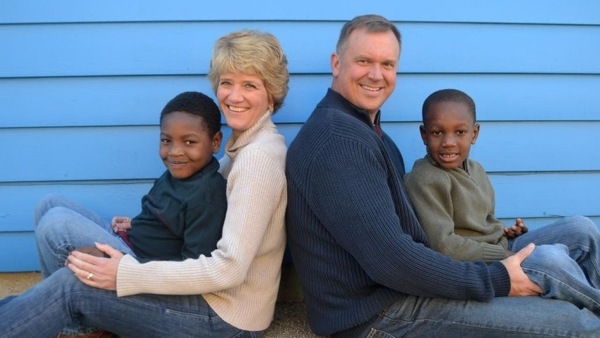 This Oct. 2015 photo provided by a friend of the family, Leanne Woods, shows Haitian brothers, Sean, left, and Jesse, posing for a portrait with their adopted parents Jodi and David Mork in Long Grove, Ill.  Sean, 8, and Jesse, 7, had been living for several years in an American-run orphanage in Haiti, God's Littlest Angels, after their mother decided she could no longer care for them. Jodi, an elementary school teacher for 25 years, left her job in order to home-school the boys they were adopted in January 2014. (Leanne Woods via AP)