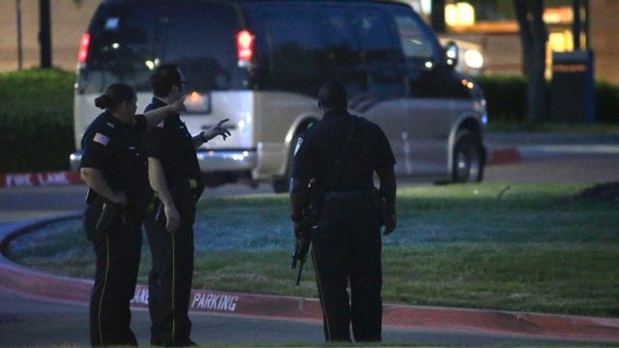 May 3, 2015: Police officers stand guard at a parking lot near the Curtis Culwell Center where a provocative contest for cartoon depictions of the Prophet Muhammad was held in Garland, Texas.