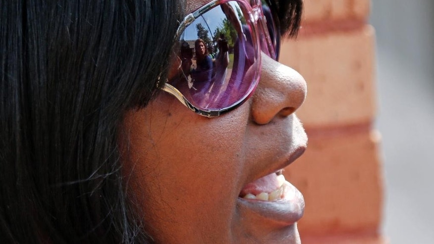 Reporters images reflect on the sun glasses of Mary Smith, the mother of brothers Marvin and Calvin Banks, who are both charged in the shooting deaths of two Hattiesburg police officers on Saturday night, as she speaks to reporters outside the Forrest County Courthouse in Hattiesburg, Miss., Monday, May 11, 2015. Older brother Marvin, 29, is charged with two counts of capital murder and his younger brother Curtis, 26, is charged with two counts of being an accessory to murder after the fact. Also involved are Joanie Calloway, 22, who is charged with two counts of capital murder and Cornelius Clark, 28, was arrested on a charge of obstruction of justice. (AP Photo/Rogelio V. Solis)