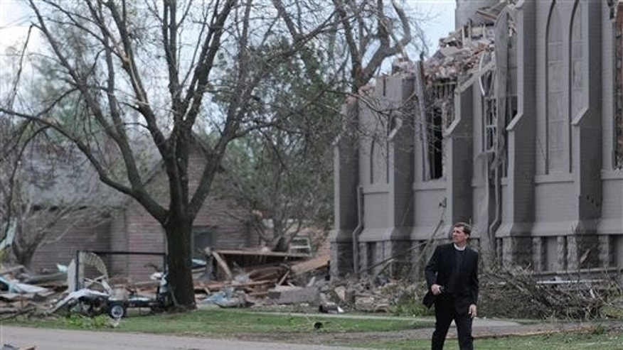 Rev. David Otten, from Immanuel Lutheran Church in Dimock, S.D., walks down Main Street in Delmont, S.D., in front of Zion Lutheran Church on Sunday, May 10, 2015, after a tornado tore through the area damaging homes and businesses on Sunday morning. Otten was filling in for Rev. Brian Bucklew at Zion Lutheran Church, but wasn't in the church when the tornado hit. The tornado hit the town southwest of Sioux Falls on Sunday morning, injuring nine people and damaging at least 20 buildings, including a century-old church. Two people remain hospitalized. Crews are working to restore water, electricity and phone service. (Joe Ahlquist/The Argus Leader via AP) NO SALES