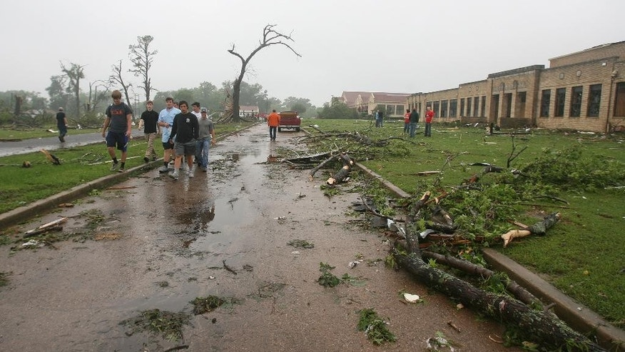 Residents of Van, Texas, make their way through storm damage near the towns Intermediate and elementary schools, Monday, May 11, 2015. Emergency responders searched through splintered wreckage Monday after a line of tornadoes battered several small communities in Texas and Arkansas, killing at least five people. (AP Photos/Todd Yates)