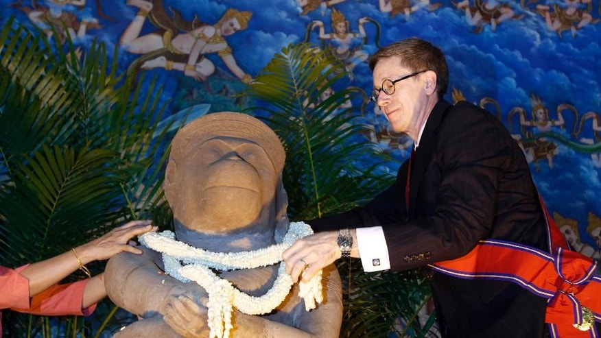 Director of the Cleveland Museum of Art William M. Griswold places a garland on a 10th century Cambodian sandstone statue during a ceremony in Phnom Penh, Cambodia, Tuesday, May 12, 2015. The Cleveland Museum of Art on Tuesday handed over a 10th-century statue to Cambodia after it uncovered evidence the sculpture was probably looted during the country's civil war. (AP Photo/Heng Sinith)