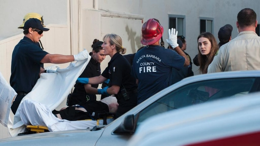In this Monday, May 11, 2015 photo, paramedics cover a victim with a sheet in Isla Vista, near Santa Barbara, Calif. Two people were shot and a third was assaulted Monday night in an attack near the University of California, Santa Barbara in the same neighborhood where a man staged a killing rampage last year. Three men in their early 20s were taken to a hospital with moderate injuries after county sheriff's deputies and campus police answered a domestic disturbance call outside a home in Isla Vista, according to fire and sheriff's officials. (Kenneth Song/Santa Barbara News-Press via AP) MANDATORY CREDIT
