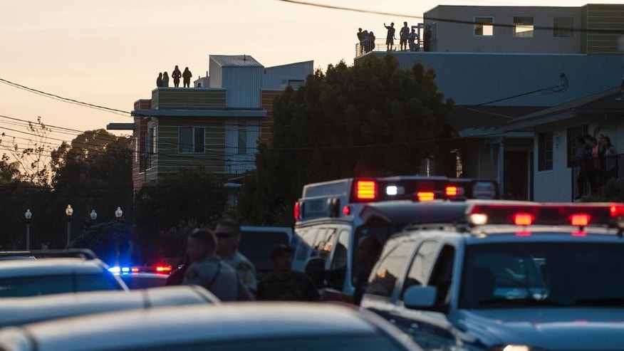 In tMonday, May 11, 2015 photo, local residents atop an apartment watch a crime scene in Isla Vista, near Santa Barbara, Calif. Two people were shot and a third was assaulted Monday night in an attack near the University of California, Santa Barbara in the same neighborhood where a man staged a killing rampage last year. Three men in their early 20s were taken to a hospital with moderate injuries after county sheriff's deputies and campus police answered a domestic disturbance call outside a home in Isla Vista, according to fire and sheriff's officials. (Kenneth Song/Santa Barbara News-Press via AP) MANDATORY CREDIT
