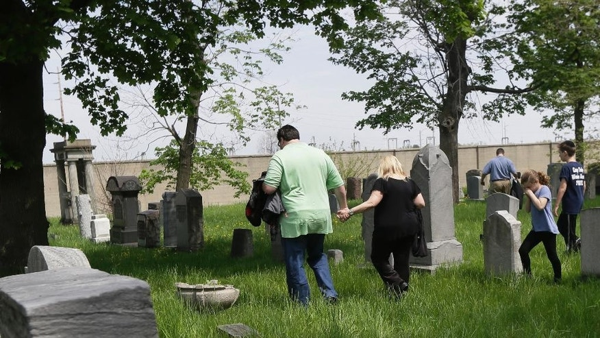In a photo from Sunday, May 10, 2015, in Hamtramck, Mich., Barbara Morse walks with her son-in-law, Ben Geller and grandchildren after visiting the grave site of her great-grandmother, Vichna Benstein, at the Beth Olem Cemetery on the grounds of the General Motors Co.'s Detroit Hamtramck Plant. Public access to the green oasis is limited to a couple days a year, including this past Sunday.  (AP Photo/Carlos Osorio)