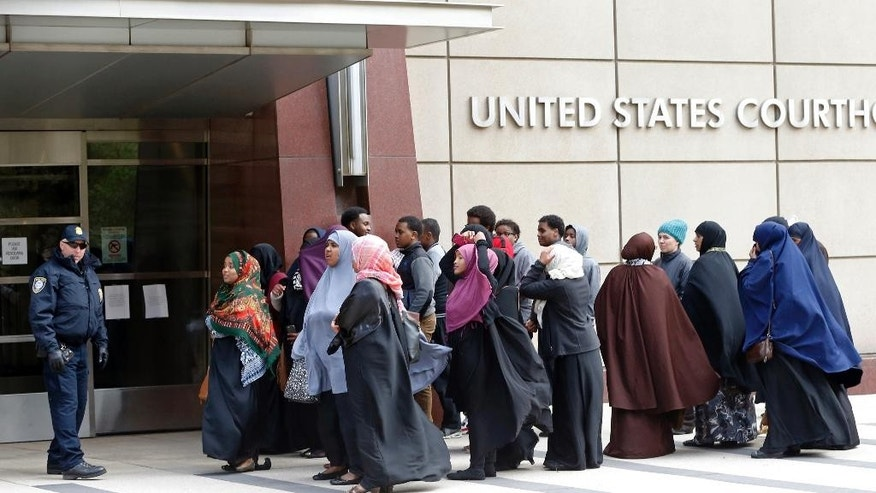 Members of the Minneapolis Somali community wait Tuesday, May 12, 2015, to enter the United States Courthouse in Minneapolis where a federal judge ordered four Minnesota men accused of trying to travel to Syria to join the Islamic State group held pending trial. (AP Photo/Jim Mone)