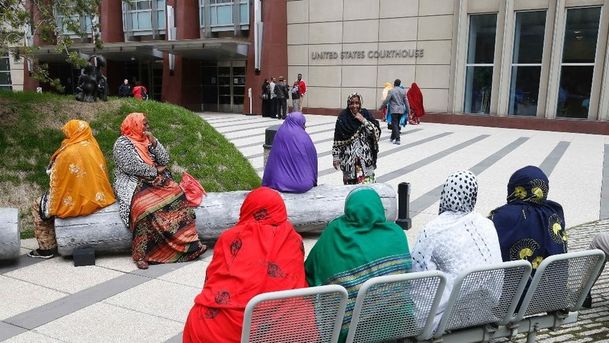 Members of the Minneapolis Somali community gather Tuesday, May 12, 2015, outside the United States Courthouse in Minneapolis where a federal judge ordered four Minnesota men accused of trying to travel to Syria to join the Islamic State group held pending trial. (AP Photo/Jim Mone)