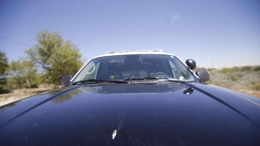 A bullet grazed the hood of a Montezuma County Sheriff's Office vehicle, Monday, May 11, 2015, driven by patrol deputy Jason Williams out of Cortez, Colo., on Bluff Road in Shiprock, N.M. Authorities say police shot and killed two people in Shiprock in connection with a chase that began in Cortez, Colo. (Jon Austria/The Daily Times via AP)