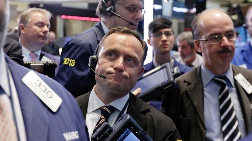 George Baskinger, center, works with fellow traders on the floor of the New York Stock Exchange, Tuesday, May 12, 2015.  U.S. stocks are opening lower following declines in European markets. (AP Photo/Richard Drew)
