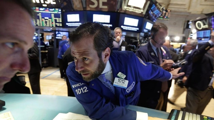 Specialists Glenn Carell, left, and Michael Pistillo, center, consult on the floor of the New York Stock Exchange, Tuesday, May 12, 2015. U.S. stocks are opening lower following declines in European markets. (AP Photo/Richard Drew)