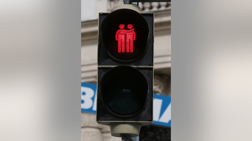 A street light with a same gender pair is pictured in dowtown Vienna, Austria, May 12, 2015. These lights were set up by city officials until June, just in time for the annual Life Ball, where celebrities will rub shoulders with party-goers dressed in little more than body paint and cross-dressers in wild costumes at the charity event supporting AIDS research. (AP Photo/Ronald Zak)