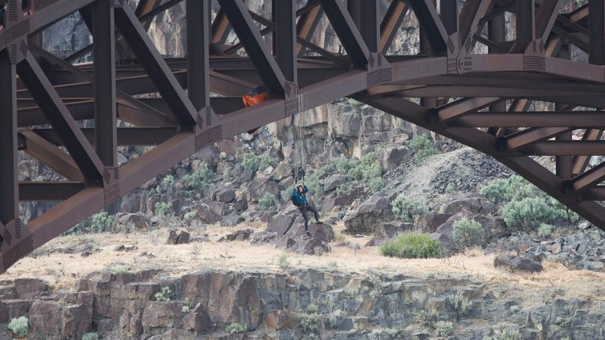A BASE jumper hangs from her parachute on supports of the Perrine Bridge on Tuesday, May 12, 2015, in Twin Falls, Idaho. (Stephen Reiss/The Times-News via AP)