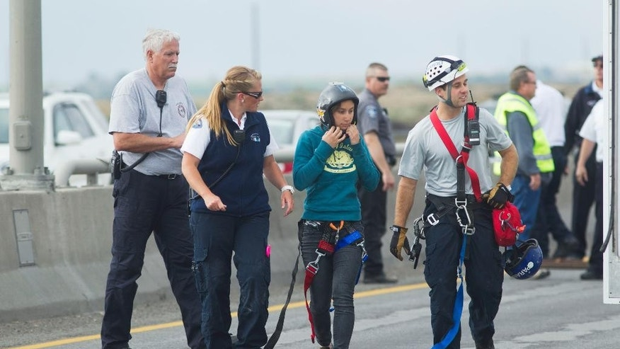 A BASE jumper after being rescued by first responders after her parachute wrapped around a support on the Perrine Bridge on Tuesday, May 12, 2015, in Twin Falls, Idaho. (Stephen Reiss/The Times-News via AP)
