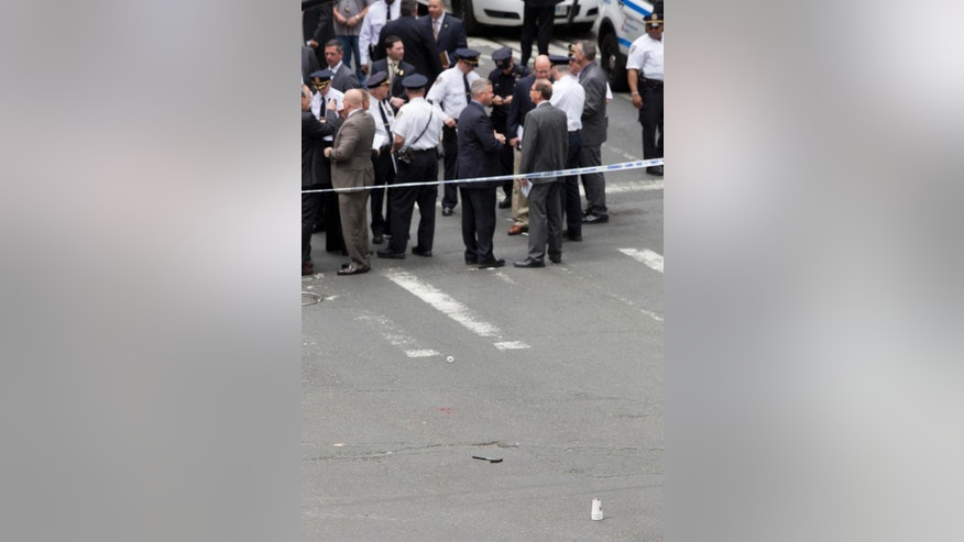 A hammer, bottom center, lies in the middle of a Manhattan intersection as police investigators gather, Wednesday, May 13, 2015, after a man apparently wielding the hammer was shot and wounded by police in New York. The shooting took place shortly after 10 a.m. Wednesday blocks from Madison Square Garden and Penn Station in Manhattan. (AP Photo/Mark Lennihan)