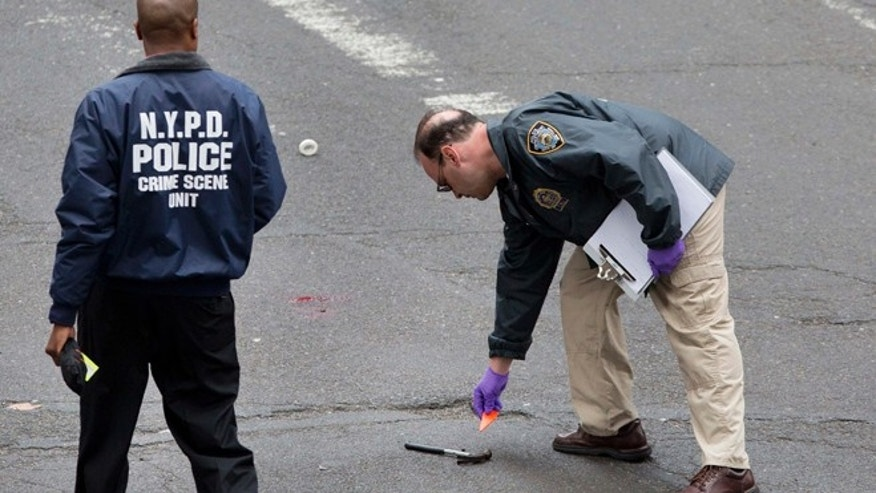 May 13: A crime scene investigator with the New York Police Department places a tag next to a hammer lying in the middle of a Manhattan intersection, in New York, after a man apparently wielding the hammer was shot and wounded by police.