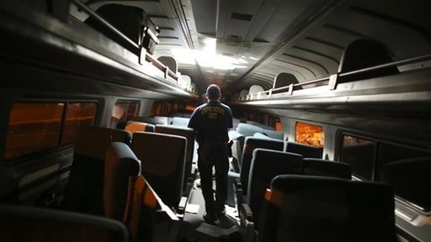 A crime scene investigator looks inside a train car after a train wreck, Tuesday, May 12, 2015, in Philadelphia. An Amtrak train headed to New York City derailed and crashed in Philadelphia. (AP Photo/Joseph Kaczmarek)