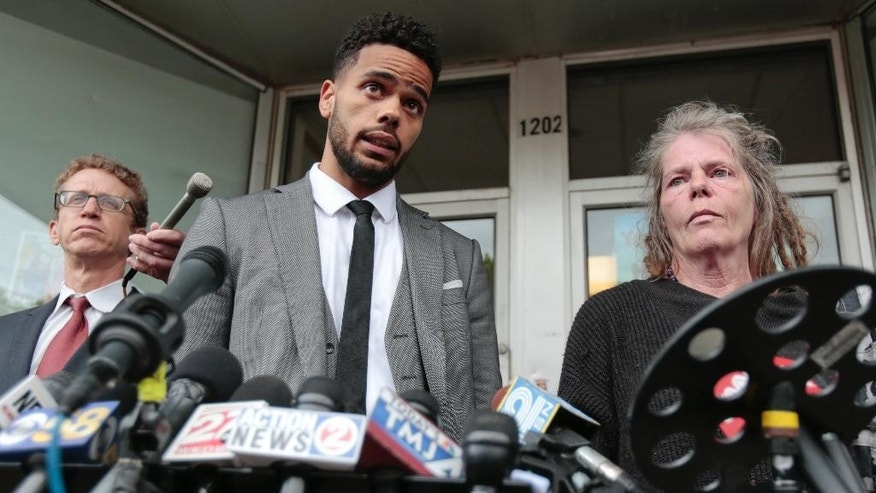 Turin Carter, center, uncle of Tony Robinson, speaks next to family attorney Jon Loevy, left, and Robinson's grandmother Sharon Irwin during a news conference at the Social Justice Center, Tuesday, May 12, 2015, in Madison, Wis. Dane County District Attorney Ismael Ozanne announced Tuesday that Madison Police Officer Matt Kenny would not face charges for the shooting death of Robinson. (M.P. King/Wisconsin State Journal via AP)