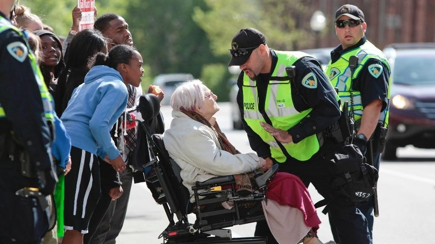 Former Alder, Barbara Vedder is stopped by a police officer from crossing Doty Street during a protest in Madison, Wis., Wednesday, May 13, 2015. Dane County District Attorney Ismael Ozanne announced Tuesday that Madison police officer Matt Kenny would not face charges for the shooting death of unarmed Tony Robinson in March. (M.P. King/Wisconsin State Journal via AP)