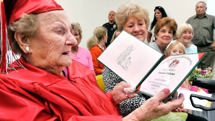 May 12, 2015: Wearing her cap & gown Lora Lois LeMond White Hardy, 99, looks over the honorary diploma from Anderson High School in Anderson, Ind.