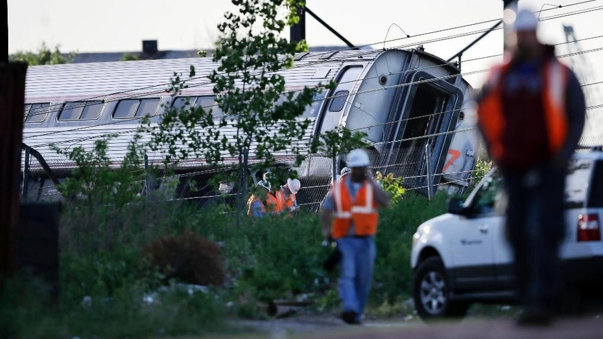 Emergency personnel walk near the scene of a deadly train wreck, Wednesday, May 13, 2015, in Philadelphia. An Amtrak train headed to New York City derailed and crashed in Philadelphia on Tuesday night. (AP Photo/Mel Evans)