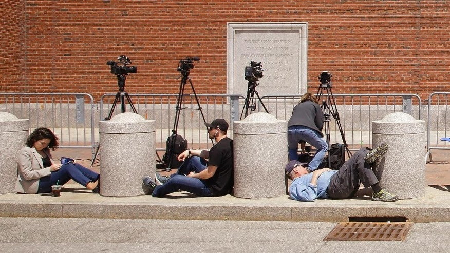 Members of the media wait outside the John Joseph Moakley United States Courthouse during the closing statements phase of the Dzhokhar Tsarnaev federal death penalty trial on Wednesday, May 13, 2015, in Boston. Tsarnaev is charged with conspiring with his brother to place two bombs near the Boston Marathon finish line that killed three and injured 260 spectators in April 2013. (AP Photo/Stephan Savoia)