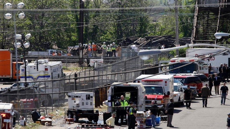 Investigators, center back, stand on the tracks near Tuesday's deadly train derailment, Thursday, May 14, 2015, in Philadelphia. An Amtrak train headed to New York City derailed and crashed in Philadelphia on Tuesday night killing at least seven people and sending more than 200 passengers and crew to area hospitals. The engineer in the deadly train derailment doesn't remember the crash, his lawyer said Thursday, complicating the investigation into why the Amtrak passenger train was going more than twice the allowed speed when it shot off a sharp curve. (AP Photo/Mel Evans)