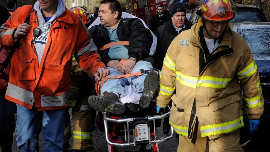 FILE - In this Dec. 1, 2013, file photo, Metro North Railroad engineer William Rockefeller is wheeled on a stretcher away from the area where the commuter train he was operating derailed in the Bronx borough of New York. Prosecutors said on Thursday, May 14, 2015, that Rockefeller, who fell asleep at the controls of a commuter train that derailed and killed four people, will not face criminal charges. (AP Photo/Robert Stolarik, File)