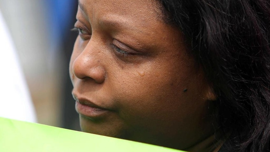 A tear runs down the eye of Katilya Rogers, aunt of Justus Howell during a protest outside the courthouse where Lake County State's Attorney Michael Nerheim announced a decision Thursday, May 14, 2015, in Waukegan, Ill., that an investigation concluded that Zion police Officer Eric Hill was justified in shooting Justus Howell on April 4. Authorities say Howell, of Waukegan, met a man to buy a handgun but then tried to steal it and Howell pointed the gun at the man during a scuffle. They say Hill intervened and chased Howell through yards and an alley, then shot him twice in the back when the teen turned slightly toward him with the gun in his hand. Nerheim says Hill feared for his life. The shooting prompted complaints of racial bias. (Steve Lundy /Daily Herald via AP)