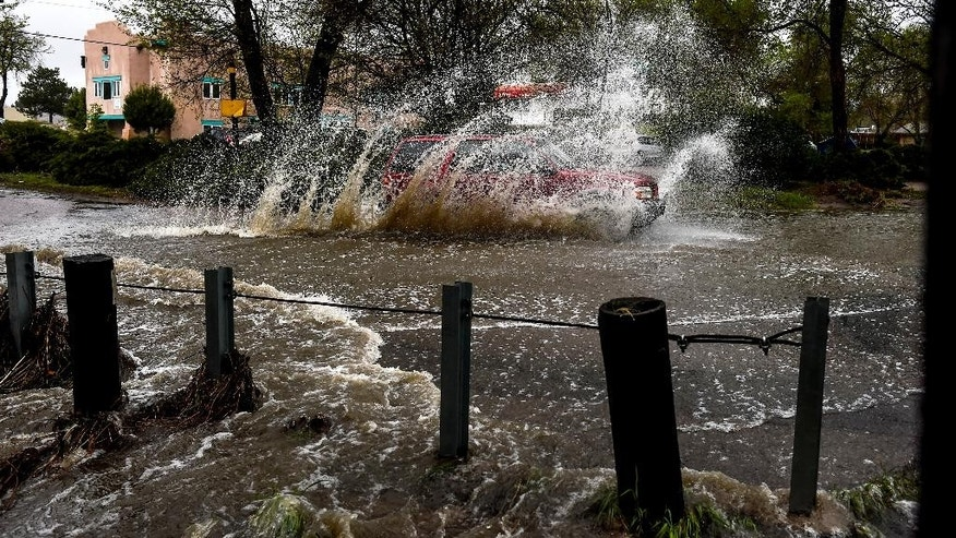 FILE - In this May 5, 2015 file photo, a car navigates a flooded intersection as a small stream empties over the road as a storm rages over Colorado Springs, Colo. While California and much of the far West are suffering through extreme drought, Colorado is splashing through a wetter-than-normal spring. (Michael Ciaglo/The Gazette via AP, file) MAGS OUT; MANDATORY CREDIT
