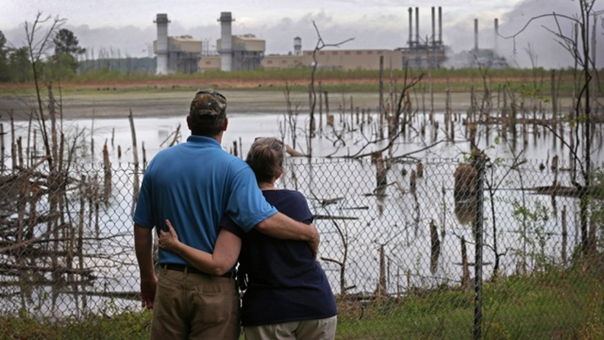 FILE - In this April 25, 2014, file photo, Bryant Gobble, left, hugs his wife, Sherry Gobble, right, as they look from their yard across an ash pond full of dead trees toward Duke Energy's Buck Steam Station in Dukeville, N.C. (AP Photo/Chuck Burton, File)