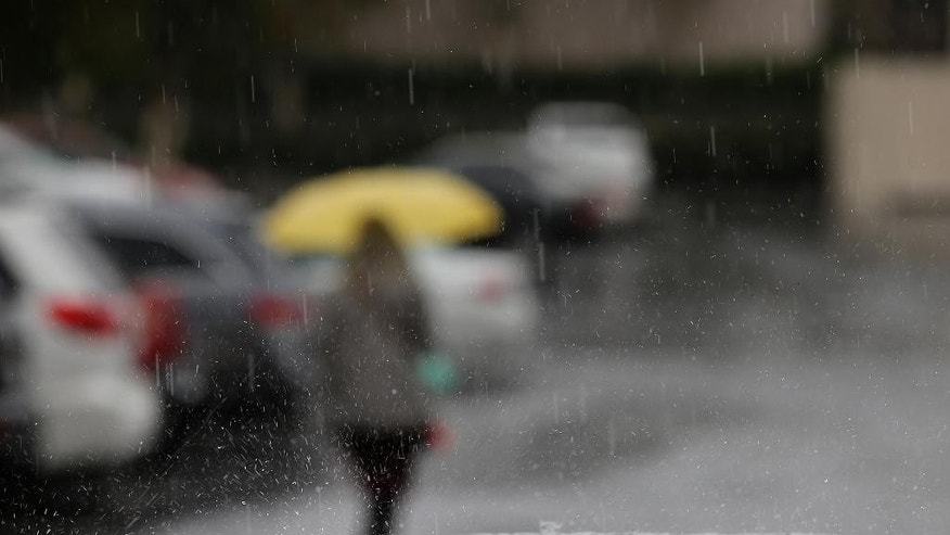 Rain drops fall on a car parked outside a building, Friday, May 15, 2015, in Buena Park, Calif. A second round of rain from a rare spring storm swept into drought-stricken Southern California on Friday, along with heavy winds, snow in the mountains and the possibility of hail and lightning. (AP Photo/Jae C. Hong)